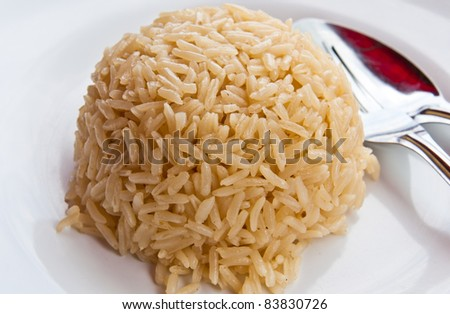 White rice on a plate, spoon on the side - stock photo
