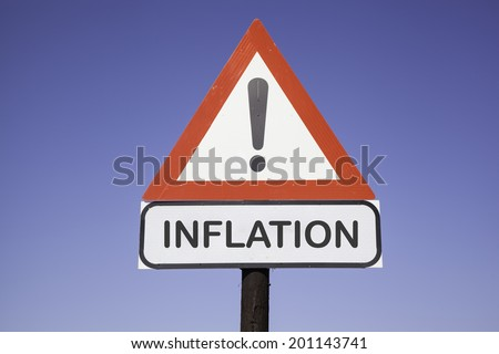 White road warning triangle with black  exclamation point and red frame on  a wooden mast in front of a blue sky. A second rectangular sign warns in english about inflation - stock photo