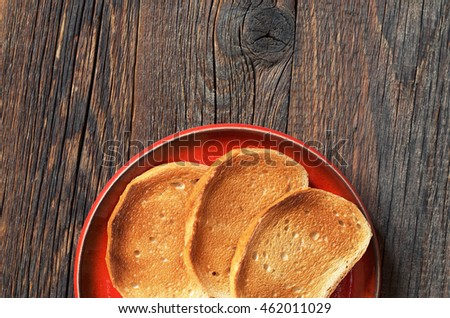 White roasted bread in red plate on dark wooden background, top view. Space for text