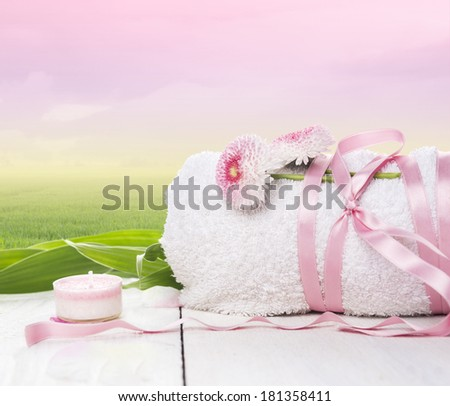 White rolled up towel, tied with Pink Ribbon with daisy flowers on wooden table,summer morning background  - stock photo