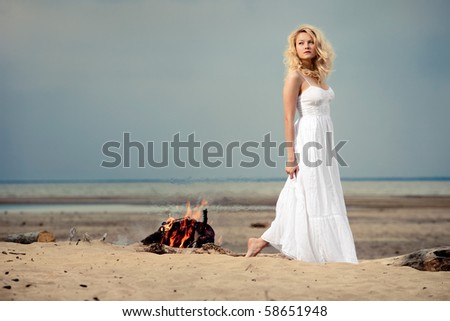 White romance. A barefoot woman wearing a white dress on the beach near an open fire. - stock photo
