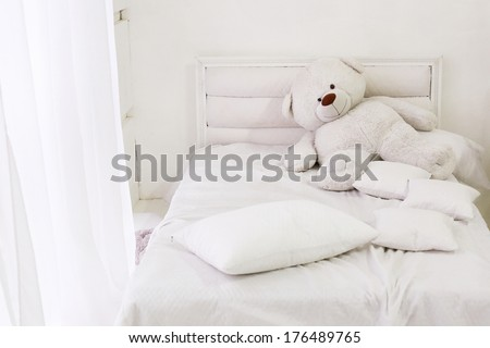 white room interior with bed, window, pillows and bear - stock photo