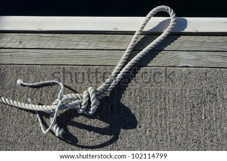 White rope on a dock. - stock photo