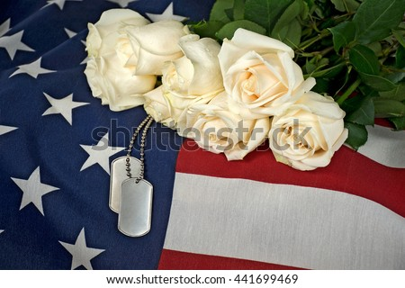 white rose bouquet and military dog tags on American flag - stock photo