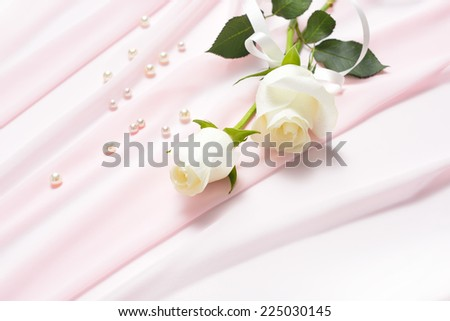 White rose flowers tied with ribbon on pink cloth with pearls