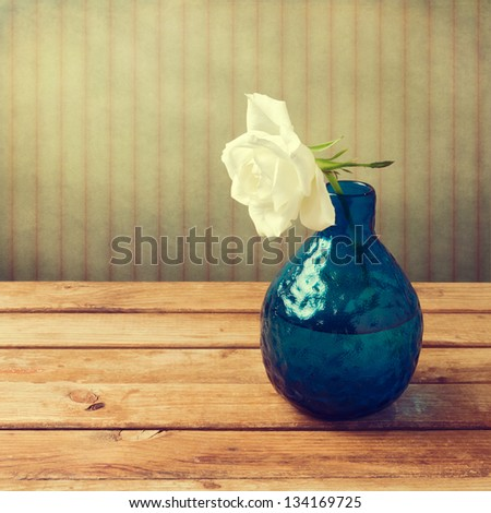 White rose in blue vase over retro background - stock photo