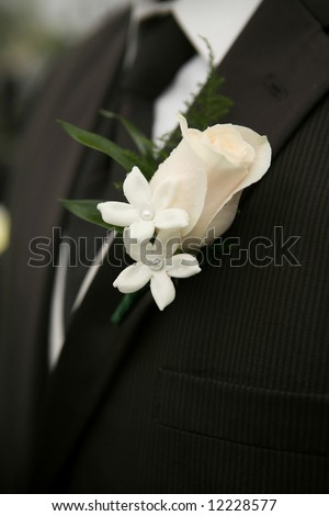 White Rose Wedding Boutonniere On Suit of Groom - stock photo
