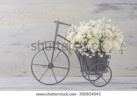 White roses in a bicycle vase - stock photo