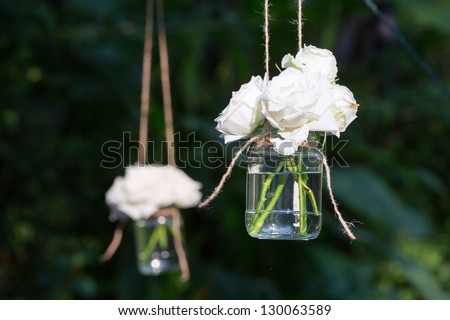 White roses in a glass vase hung in a wedding party - stock photo