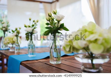 White roses in glass bottles and vases on wooden table. Wedding decorations. Rustic style. - stock photo