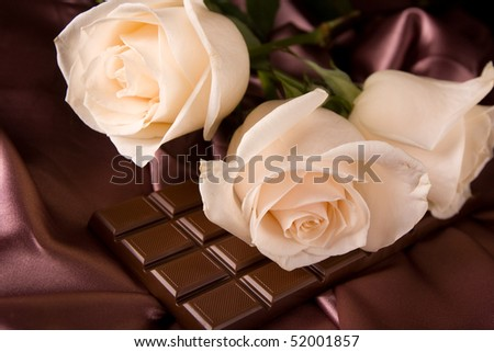 White roses on brown silk and chocolate - stock photo