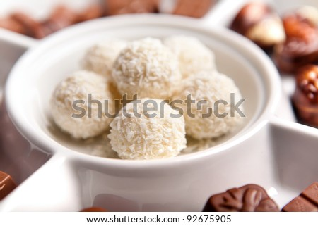 White, round, coconut chocolate sweats  on plate with other chocolate in background