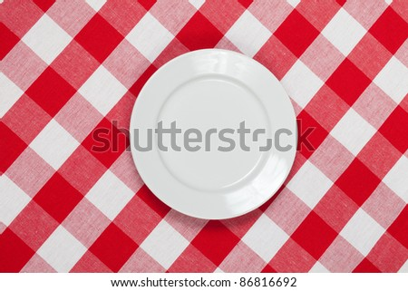 white round plate on red checked tablecloth - stock photo