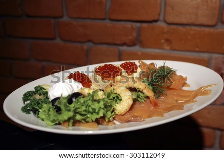 White round plate with many different kinds of seafood of red salmon caviar shrimp bread butter yellow lemon black olive berry lettuce and greenery on brown brick wall background, horizontal picture - stock photo