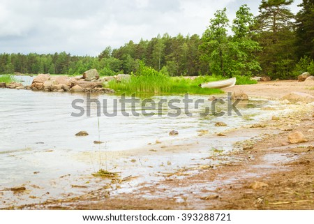 White rowing boat stands on a sandy shore in a quiet Bay of the Finnish Gulf. Area for summer camping in the woods. Hamina, Finland, Suomi - stock photo