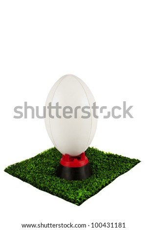 White rugby ball on tee placed on a patch of grass ready for kicking - stock photo