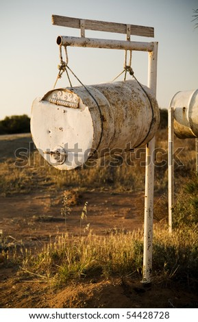 White rusting barrel hanging from a pole forms a country letterbox / mailbox - stock photo