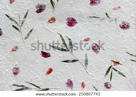 White Sa Paper with rose petals  and bamboo leaves background, Sa Paper is  hand made paper from parish Bosang province Chiang Mai north of Thailand, Mulberry paper texture background - stock photo