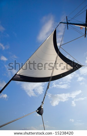 White sail and pulley rigging against blue sky - stock photo