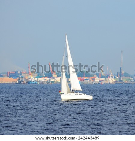 white sail yacht against large black cruise liner ship in port o - stock photo