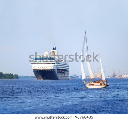 white sail yacht against large black cruise liner ship in port of Riga - stock photo