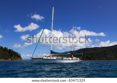 white sail yacht in coral sea at whitsunday islands ashore blue water and sky with clouds summer time - stock photo