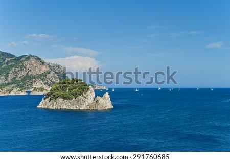 white sailboats in Aegean sea floating among rocky islands on sunny day near Marmaris, Turkey - stock photo