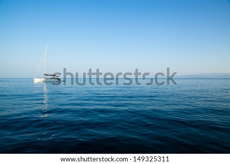 White sailing boat on calm waters - stock photo