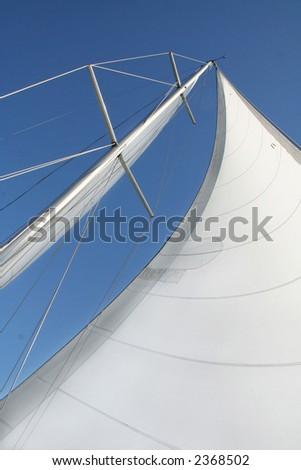 White sails against a blue sky. - stock photo
