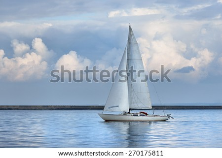 White sails yacht sailing in a calm sea. Riga, Latvia - stock photo