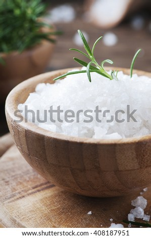 White salt and green rosemary on the wooden table, selective focus