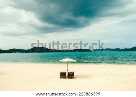 white sand beach resort with two sunbeds and umbrella with no people, stormy sky, holiday resort in Vietnam, Hon Tam beach - stock photo