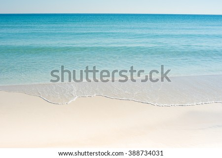 white sand beach with blue green waves - stock photo