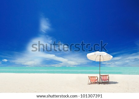 White sand beach with chairs and cloudy blue sky - stock photo