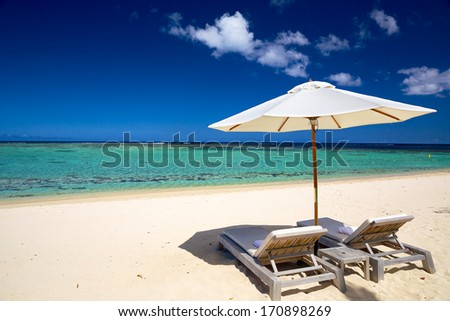 White sand beach with deckchairs and umbrella in tropical Island - stock photo