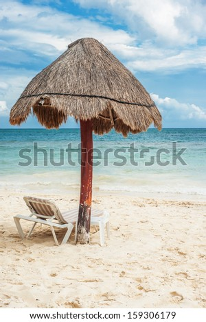 White sand Mexican beach with umbrella and lounge chair