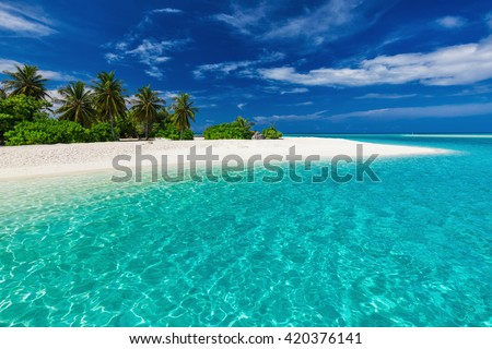 White sandy tropical beach with palm trees and blue lagoon on sunny day - stock photo