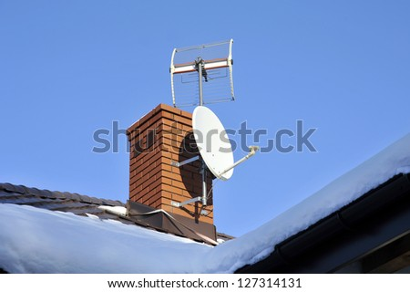 White satellite dish attached to the brown roof - stock photo