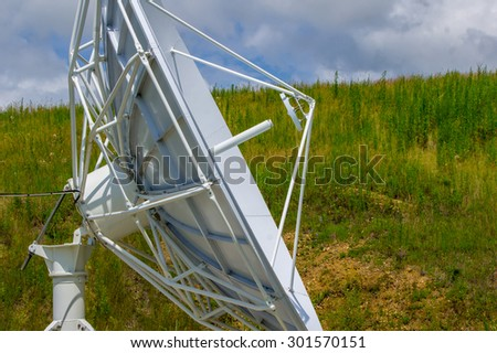 White satellite dishs on the background of green grass and blue sky - stock photo