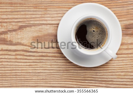 White saucer and cup of fresh hot coffee with foam on rustic wooden table background. Top view with space for text. Coffee cup at right side. Concept is fresh natural morning coffee as energy source. - stock photo