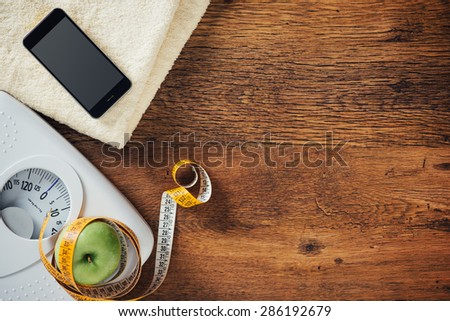 White scale, apple wrapped in a tape measure, towel and smart phone on a wooden table, weight loss and dieting concept - stock photo