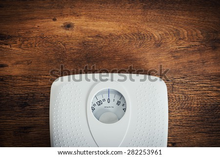 White scale on a wooden table top view, fitness and weight loss concept - stock photo