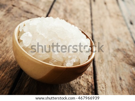 White sea salt in brown bowl on dark wooden texture background in still life style