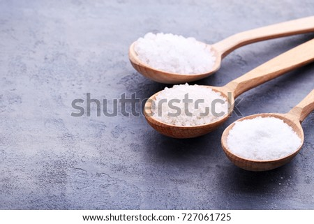 White sea salt in spoons on grey wooden table