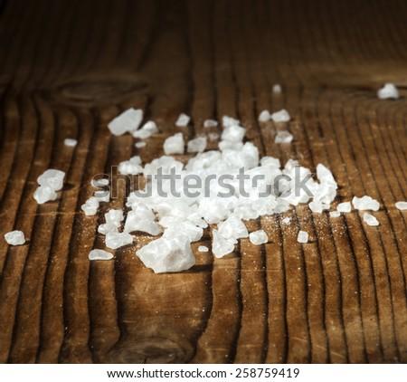 White sea salt on a wooden background. - stock photo