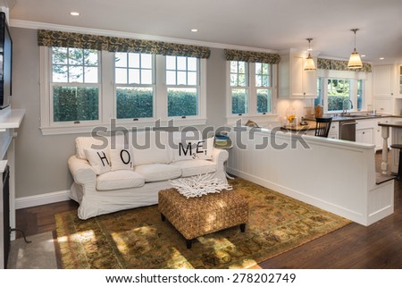 White seating arrangement, couch, sofa in mid century modern home with open floor plan and kitchen. - stock photo