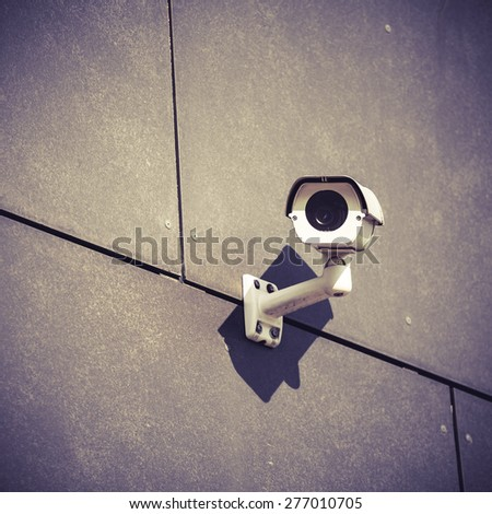 White security camera on gray office building, safety surveillance system outside looking around in city urban scene, cctv electronics industry concept - stock photo
