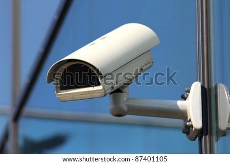 white security CCTV camera on glass facade - stock photo