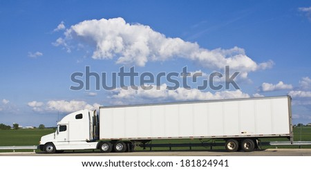 White Semi-truck against green field and cloudy sky. - stock photo