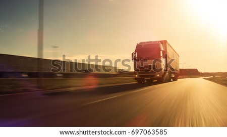 White Semi Truck with Cargo Trailer Attached Drives on the Empty Road. Industrial Warehouses by the Sides of the Highway. Sunset. Blur motion.